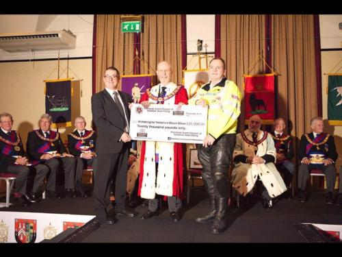 The guests from White Knights receive a cheque for £20,000 to pay for the Blood Bike
